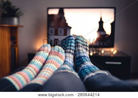 Couple With Socks And Woolen Stockings Watching Movies Or Series On Tv In Winter. Woman And Man Sitt