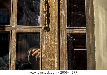 The Cleaner's Hand With Red Nails Is Visible Through The Door Glass