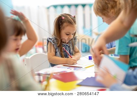 Group Of Children Drawing With Nursery Teacher In Kindergarten