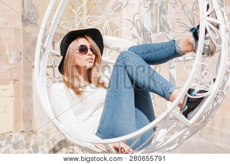 Stylish Attractive Young Hipster Woman In An Elegant Black Hat In A White Knitted Sweater In Stylish