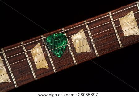 Green Guitar Pick On The Fingerboard And Dark