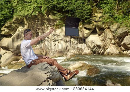 Man Throws Out Laptop Sitting At The Bank Of River Over The Waterfall. Tired From Work Concept