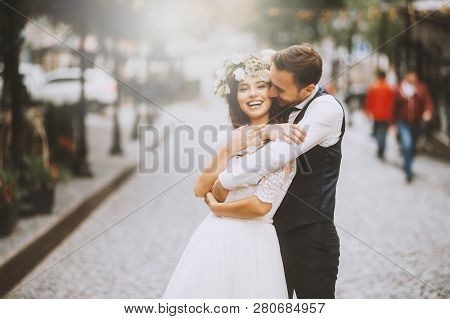 Handsome Loving Couple, Wife And Husband, Hugs Tender His Wife From Back In The Street