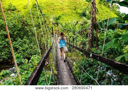 Young Woman Walking On Suspension Bridge Over Wainibau Stream, Lavena Coastal Walk, Taveuni Island,