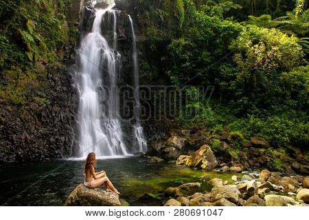 Young Woman In Bikini Sitting By Middle Tavoro Waterfalls In Bouma National Heritage Park On Taveuni