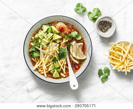 Crock Pot Vegetarian Quinoa Tomato Soup With Corn Tortilla Chips, Avocado And Cilantro On Light Back