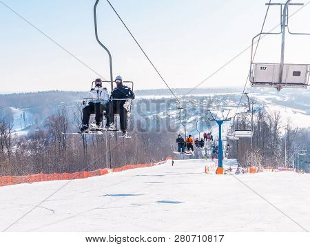 Skiers And Snouborders On A Ski Lift Pov In Winter Time. The Cable Car Lifts The Peoples Up To The S