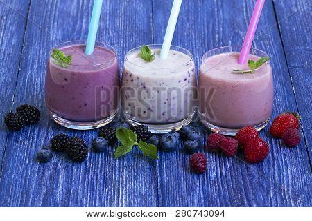 Raspberry, Strawberry, Blackberries, Blueberry Smoothie On Blue Wooden Background. Milkshake With Fr