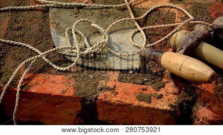 Used and dirty masonry tools like masonry trowel, plumb bob, bricklayer hammer laying on a brick wall, selective focusing poster
