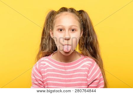 Girl On Yellow Background Sticking Tongue Out. Cute Antics And Frolicking Concept.