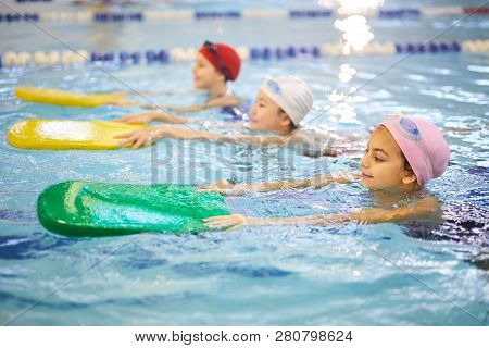 Young Girl In Swimwear And Swimming Cap Using Boards In The Swimming Pool,  They Learning To Swim
