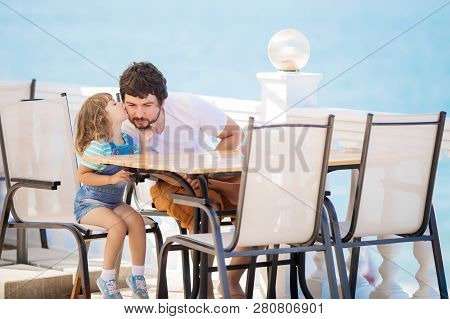 Father And Daughter Sitting At The Outdoors Restaurant, Sea At The Background. Family Lifestyle. Lit