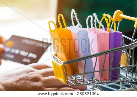 Paper Shopping Bags In Trolley And Hand Holding Mock Up Of Credit Card And Another Hand Is Using Lap