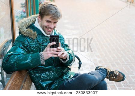 Man Unshaven Wear Warm Jacket And Hold Smartphone Snowy Urban Background. Communication Concept. Hip