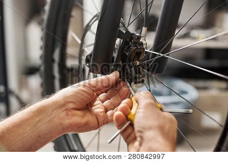 Cropped Shot Of Male Repairer Working In Bicycle Repair Shop, Mechanic Repairing Bike Brakes Using S