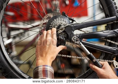 Point Of View Male Mechanics Hands In Bicycle Repair Shop, Repairing Bike Using Special Tool