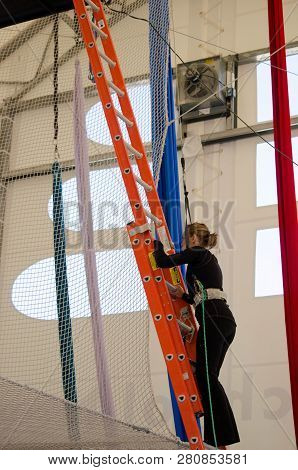 An Adult Female Trapeze Artist Climbs A Ladder Leading Up To A Trapeze Platform To Perform A Jump