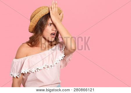 Indoor Shot Of Stressful Woman Keeps Hand On Forehead, Recalls Something In Mind, Wears Headgear, Fo
