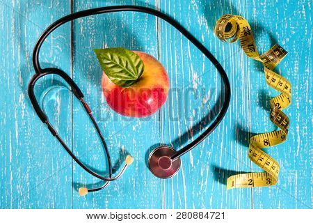 Apple, Measuring Tape And A Stethoscope On The Table, Health Concept.