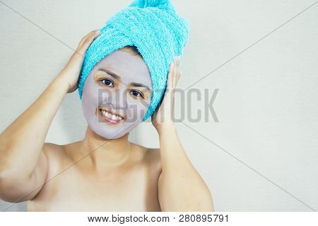 Happy Woman With A Clay Mask. Photo Of Attractive Young Woman With Towel On Her Head On Beige Backgr