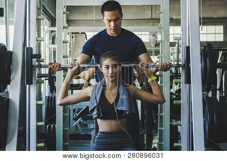 Personal Fitness Trainer Assisting A Young Woman With Workout - Image