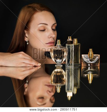Beautiful woman and collection of perfumes bottles on dark background.