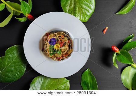 Stir-fried Spicy Spaghetti With Seafoods On Black Background.