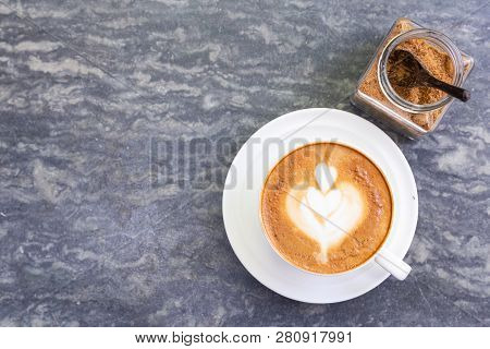 Top View Of Hot Coffee With Heart Pattern In White Cup And Brown Sugar On Stone Table Background. A