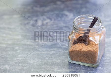 Brown Sugar With Wooden Spoon In Glass Bottle On Gray Stone Table In Coffee Shop. Sugar Granulated B