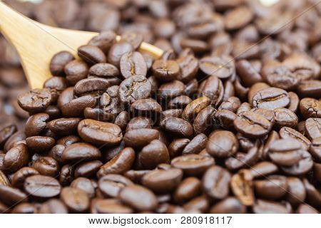 Coffee Beans Texture Or Coffee Beans Background With Wooden Spoon Background. Brown Roasted Coffee B