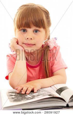 Retrato de Linda chica mirando a cámara mientras leía el libro interesante