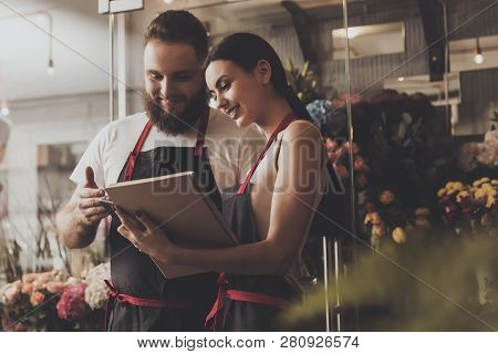 Portrait Of Smiling Florists Man And Woman. Beautiful Florist Girl Makes Working Notes In Notebook.