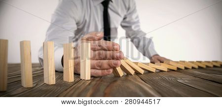Chain Reaction In Business Concept, Businessman Intervening Dominoes Toppling poster