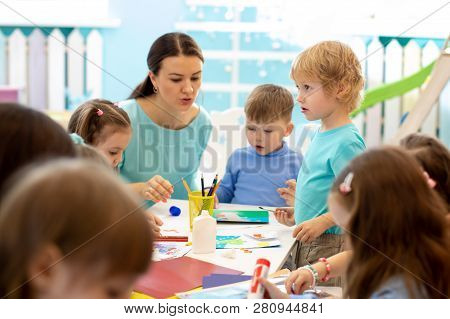 Kindergartener Teaches Children Handcraft At Nursery Or Playschool