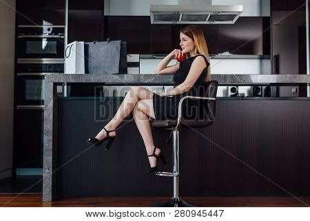 Full-length Portrait Of Elegant Woman With Fair Hair Wearing Black Dress And High Heels Sitting On A