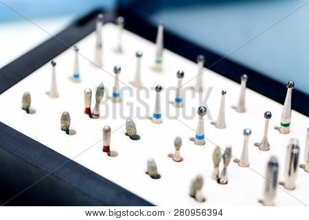 Dental nozzles or drill heads for the drill in a box. Dental bur equipment. Dental hygiene and healthcare concept. poster