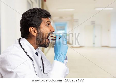 Indian Male Doctor Or Medic Eating Medicine Blisters As Addiction Or Exaggeration Concept Close-up W