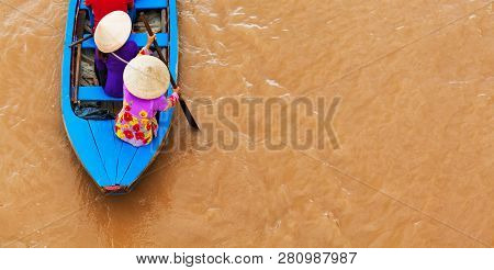 Vietnamese Old Woman On Traditional Boat Paddling By Yellow Brown Water In Canal. Mekong River Delta