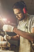 Bearded craftsman making wooden part on professional belt sander while working in joinery poster