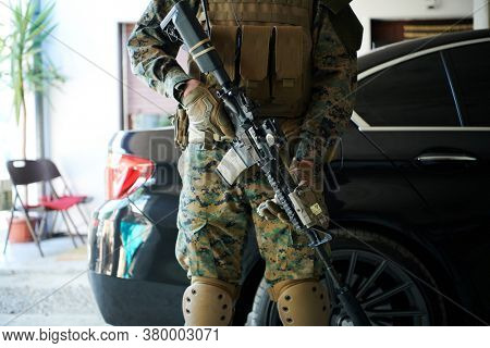 soldier protecting armored luxury vehicle a security guard in military uniform and assault  weapon bulletproof car