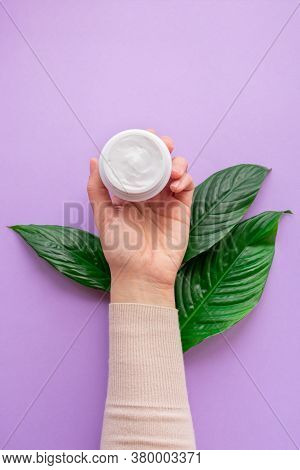 Young Girls Hand Is Nearby Jar With White Soft Hand And Body Cream On Purple Background With Large G