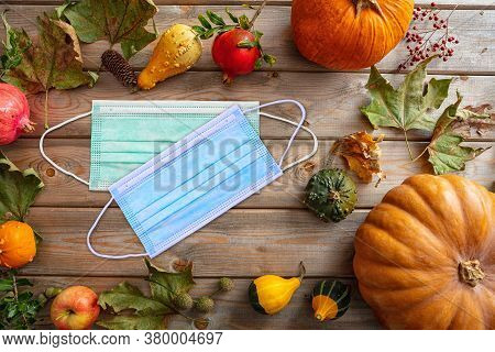 Protective Mask And Thanksgiving Pumpkins Against Wooden Background
