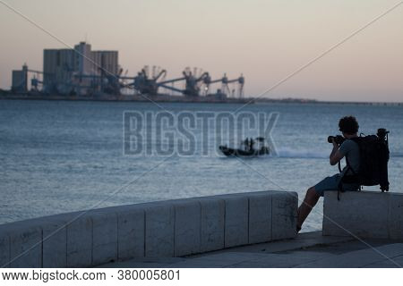 Male Silhouette With Photo Camera And Tripod. Man Is Taking Pictures Of The Seaport In The Afternoon