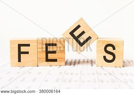 Wooden Blocks With The Text: Fees. Fixed Price Charged For A Specific Service. Business And Finance