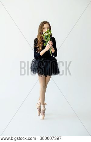 A Young Beautiful Ballerina Girl Stands On Pointe Shoes In Black Swimsuit And Skirt With Flowers In
