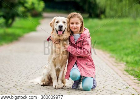 Little girl with golden retriever in park