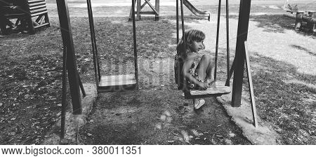 A Child Of 6 Years Old Sits On A Swing And Sings. The Girl Is Alone In The Playground. Monochrome Bl