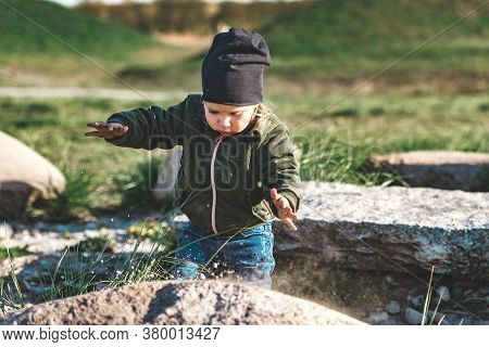Young Girl Playing With Sand On The Rock, Like A Magic