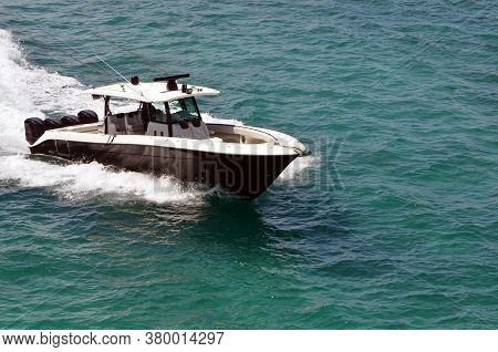 Black Sport Fishing Boat With White Trim Powered By Four Outboard Engines Speeding On Biscayne Bay O