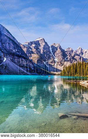 Unidentifiable Visitors Canoeing Their Boats On Turquoise-colored Moraine Lake In The Canadian Rocki